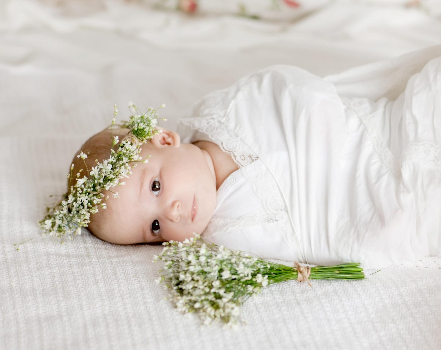 Baby swaddled in a white blanket, wearing a flower crown of baby's breath, laying on a bed